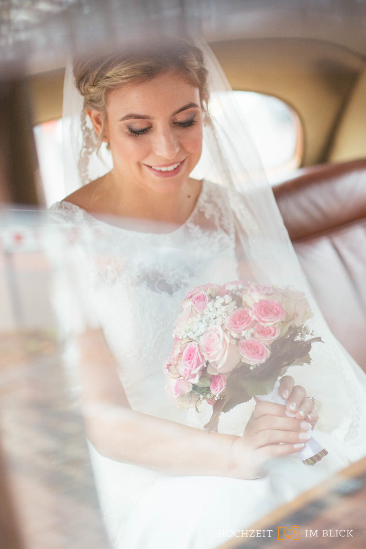 Die Braut im Oldtimer auf dem Weg zur Hochzeit