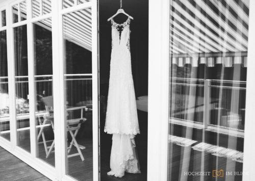 Das Brautkleid von Magdalena hängt in einer Tür an der Location Hoher Darsberg