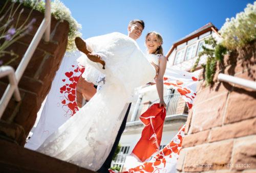 Sebastian trägt Magdalena nach der Freien Trauung an der Hochzeitslocation Hoher Darsberg