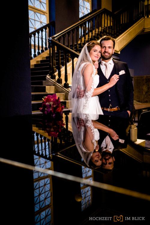 Hochzeitsfotos im Winter: Ein Brautpaar steht iin der Lobby eines Hotels in Düsseldorf. Fotografiert von unserem Hochzeitsfotografen Stefan