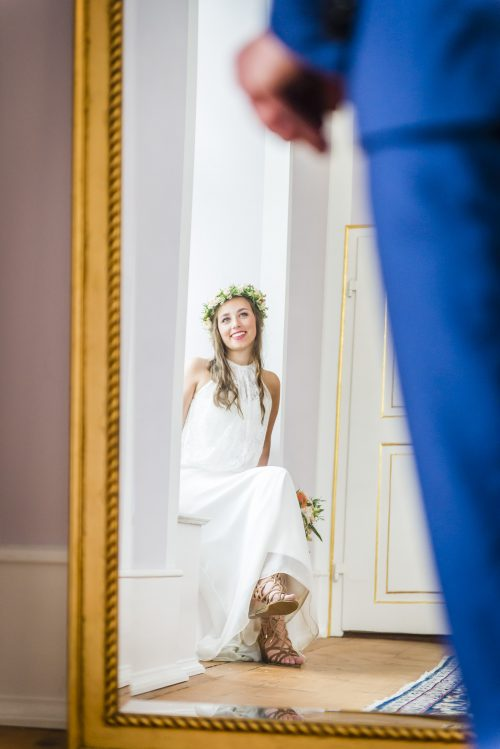 Hochzeitsfotos im Winter können gut in großen Räumen mit Fenstern entstehen, wie hier mit einer Spiegelung im Schloss von Hammerstein